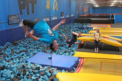 In this July 31, 2013, photo, Hunter Gottfredson,  left, 15, of Elk Ridge, flips at the Get Air Hang Time indoor trampoline park in Orem. Indoor trampoline parks have cropped up around the country in recent years, offering customers a chance to bounce, flip and jump in wall-to-wall trampolines. The jump gyms offer the kind of rain-or-shine suburban entertainment popular for birthday parties and summer camps. But some doctors and officials say the parks are dangerous and can cause serious injuries.  (AP Photo/Rick Bowmer)
