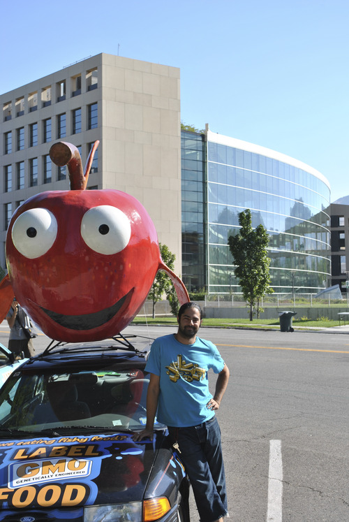Matthew Piper  |  The Salt Lake Tribune On Tuesday in Library Square, Nikolas Schiller sits besides Goldie the apple, which he is driving 3,300 miles across the country to raise awareness of GMO foods.