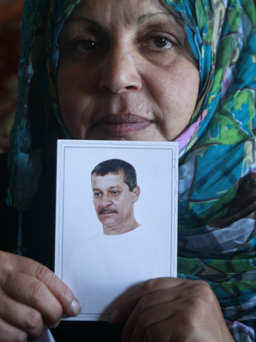 Fatima Nashabat, the wife of Mohammed Nashabat, poses with his picture at her home in the Bureij Refugee Camp, central Gaza Strip, Monday, Aug. 12, 2013. Nashabat is one of the 26 Palestinian prisoners, most of them held for deadly attacks and most have already served around 20 years, Israel agreed to release this week as a part of a U.S.-brokered deal that led to a resumption of Mideast negotiations. (AP Photo/Hatem Moussa)