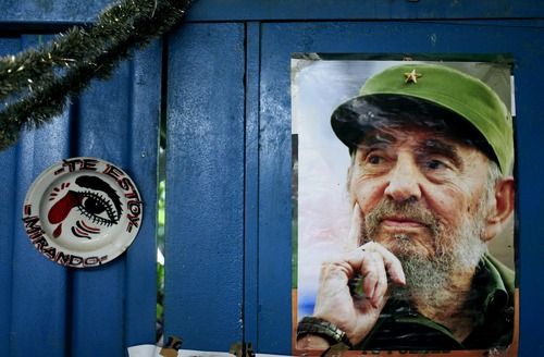 """A poster of Cuba's Fidel Castro hangs on the wall of a food market next to plate that reads in Spanish """"I'm looking at you"""" in Havana, Cuba, Tuesday, Aug. 13, 2013. Castro turns 87 on Tuesday. Castro's brother Raul Castro has been in power since a near-fatal illness forced Fidel to step aside in 2006. (AP Photo/Franklin Reyes)"""
