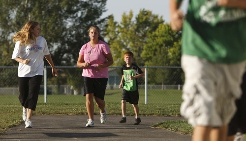 Leah Hogsten | The Salt Lake Tribune Julianne Orton, 15, (center) jogs two miles with her mother Ammi (left), brother Jacob, 6, (right) and other three siblings throughout their neighborhood Wednesday, Aug. 7, 2013.  The Orton children go to online charter schools, which allows them to arise later every morning than peers in traditional schools, a plus for teenagers whose circadian rhythms make them nightowls.