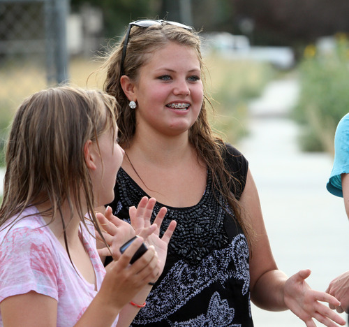 Rick Egan  | The Salt Lake Tribune   Kelsey Perkes laughs with Julianne Orton, 15 (right) as they gather vegetables from the Community Garden, with the West Point Youth Council, Wednesday, Aug. 7, 2013. Orton attends an online charter school, which allows her to arise later on school mornings than do her peers in traditional schools.