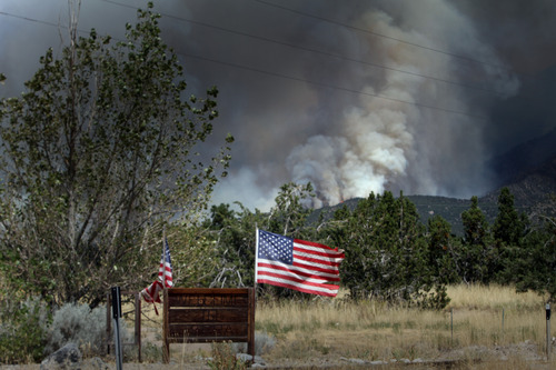 Rick Egan  | The Salt Lake Tribune   The Skull Valley fire burns as a sign welcomes guests to the town of Terra, Monday, August 12, 2013.
