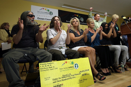 "Lottery winner Brian W. McCarthy raises his arms as other winners applaud   Tuesday, Aug. 13, 2013, in Toms River, N.J. The ""Ocean's 16,"" as a group of 16 public employees on the Jersey shore has been dubbed after snagging one of three winning tickets in last week's $448 million Powerball jackpot, gathered at an afternoon news conference in Toms River, where they work for the Vehicle Services department. The event comes one day after the nine women and seven men claimed their share of the jackpot.(AP Photo/Mel Evans)"