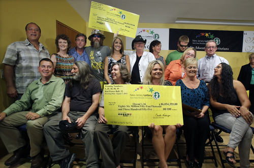 "Sixteen lottery winners pose for a photograph Tuesday, Aug. 13, 2013, in Toms River, N.J. The ""Ocean's 16,"" as the group of Ocean County public employees, who work for work for the Vehicle Services department, on the Jersey shore has been dubbed after snagging one of three winning tickets in last week's $448 million Powerball jackpot, gathered Tuesday to discuss the windfall. The event comes one day after the nine women and seven men claimed their share of the jackpot. (AP Photo/Mel Evans)"