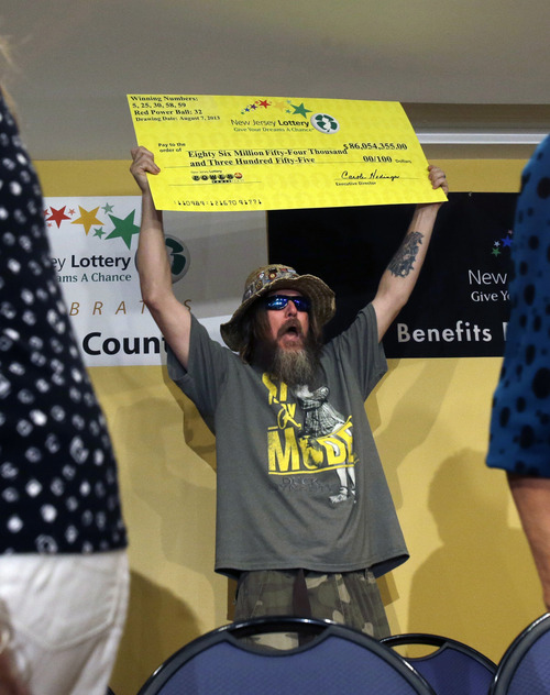 "Lottery winner William L. Seeley shouts as he holds up a sign made as a check Tuesday, Aug. 13, 2013, in Toms River, N.J. The ""Ocean's 16,"" as a group of 16 public employees on the Jersey shore has been dubbed after snagging one of three winning tickets in last week's $448 million Powerball jackpot, gathered at an afternoon news conference in Toms River, where they work for the Vehicle Services department. The event comes one day after the nine women and seven men claimed their share of the jackpot. (AP Photo/Mel Evans)"