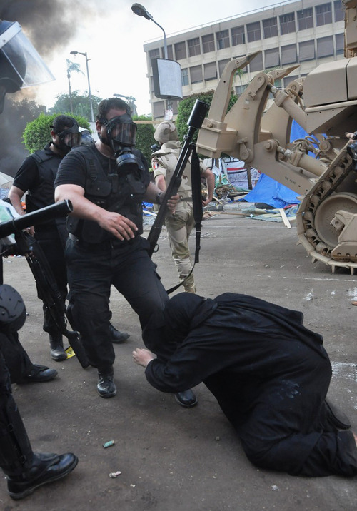 An Egyptian security force confronts a woman at a sit-in camp set up by supporters of ousted Islamist President Mohammed Morsi near Cairo University in Cairo's Giza district, Egypt, Wednesday, Aug. 14, 2013. Egyptian police in riot gear swept in with armored vehicles and bulldozers Wednesday to clear the sit-in camp and the other encampment set up by supporters of the country's ousted Islamist president in Cairo, showering protesters with tear gas as the sound of gunfire rang out. (AP Photo/Hussein Tallal)