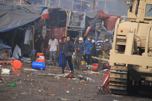 Protesters throw stones at Egyptian security forces trying to clear a sit-in by supporters of ousted Islamist President Mohammed Morsi in the eastern Nasr City district of Cairo, Egypt, Wednesday, Aug. 14, 2013. Egyptian security forces, backed by armored cars and bulldozers, moved on Wednesday to clear two sit-in camps by supporters of the country's ousted President Mohammed Morsi, showering protesters with tear gas as the sound of gunfire rang out at both sites. (AP Photo/Ahmed Gomaa)