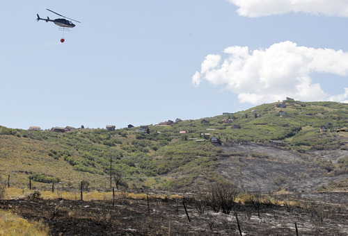 Al Hartmann  |  The Salt Lake Tribune A helicopter flies from Rockport Reservoir after dipping water into its bucket to drop on hot spots above the Rockport Estates. They made hundreds of trips on Wednesday. The fire flared up again Wednesday afternoon.