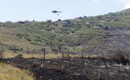 Al Hartmann  |  The Salt Lake Tribune A helicopter makes a return trip to Rockport Reservoir to dip water into its bucket to drop on hot spots above the Rockport Estates.  They made hundreds of trips on Wednesday. The fire flared up again Wednesday afternoon.