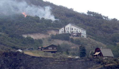 Al Hartmann  |  The Salt Lake Tribune A hot spot bursts into flame above homes in Rockport Estates Wednesday afternoon.