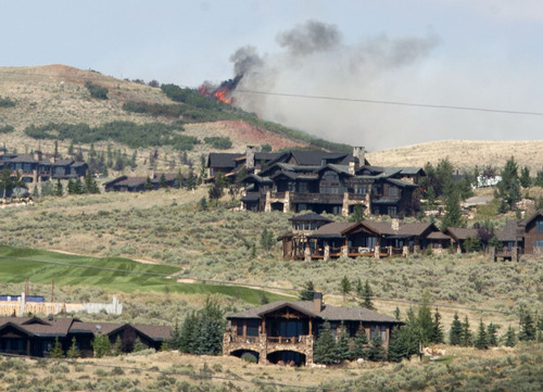 Steve Griffin | The Salt Lake Tribune  Flames leap from a ridge line above the Promontory development as the Wanship 5 wildfire continues to burn Wednesday August 14, 2013.