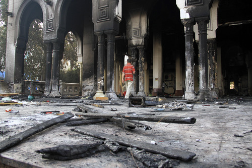 CAPTION ADDITION, ADDS DATE -- Egyptians walk among the burned remains of the Rabaah al-Adawiya mosque, in the center of the largest protest  camp of supporters of ousted President Mohammed Morsi, that was cleared by security forces, in the district of Nasr City, Cairo, Egypt, Thursday, Aug. 15, 2013. The death toll keeps going up in Egypt after security forces swept through two sit-in sites yesterday, operated by supporters of former President Mohammed Morsi. An Egyptian Health Ministry spokesman now says over 400 people died in the violence that has prompted international criticism. (AP Photo/Ahmed Gomaa)