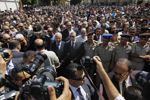 Egyptian Interior Minister Mohammed Ibrahim, center, and top officers of the army and police, march during a military funeral of policemen killed during Wednesday's clashes in Cairo, Egypt, Thursday, Aug. 15, 2013. Egyptian authorities on Thursday significantly raised the death toll from clashes the previous day between police and supporters of the ousted Islamist president, saying hundreds of people died and laying bare the extent of the violence that swept much of the country and prompted the government to declare a nationwide state of emergency and a nighttime curfew. (AP Photo/Amr Nabil)
