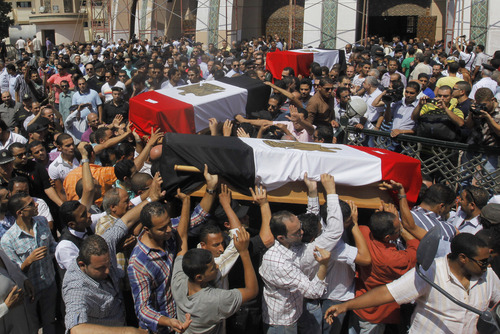 Egyptian relatives and colleagues of policemen who were killed during Wednesday's clashes carry coffins covered with national flags during a military funeral in Cairo, Egypt, Thursday, Aug. 15, 2013. Egyptian authorities on Thursday significantly raised the death toll from clashes the previous day between police and supporters of the ousted Islamist president, saying hundreds of people died and laying bare the extent of the violence that swept much of the country and prompted the government to declare a nationwide state of emergency and a nighttime curfew. (AP Photo/Amr Nabil)