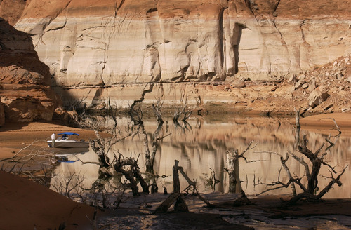 Trent Nelson  |  Tribune file photo Morris Christensen stands next to his boat on a sandbar in Forgotten Canyon exposed by the low water level in Lake Powell in 2003. Low flows on the Colorado River have forced water authorities to take the historic step of reducing the outflow of water from Glen Canyon Dam, which forms Lake Powell, creating great concern among downstream users such as Las Vegas.