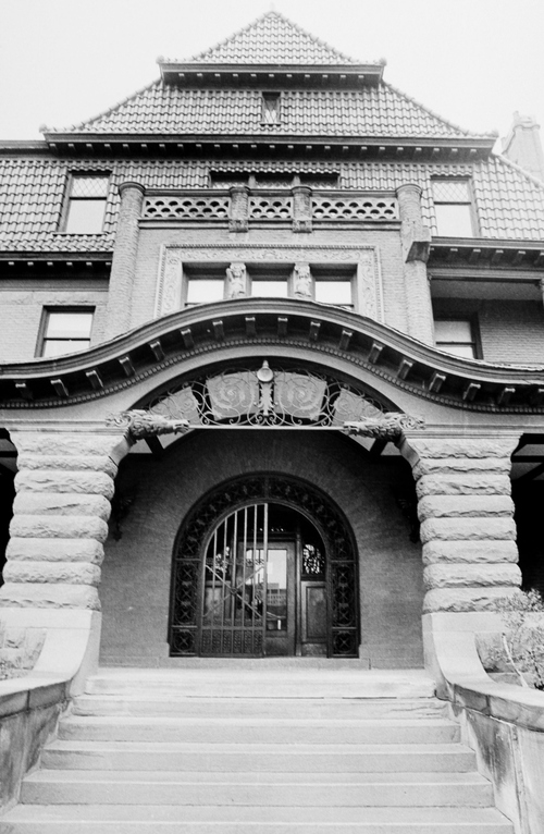 Salt Lake Tribune archive  Exterior of the home of Alfred William McCune in Salt Lake City. The home, located on north Main Street, cost $500,000 to build in 1901. McCune was a very successful business man with ventures in railroad and mining. He was a partner in the Peruvian Cerro de Pasco mines along with J. P. Morgan, William Randolph Hearst, and Frederick William Vanderbilt. McCune wanted his home to be extravagant. The McCune home site was chosen to rise up impressively over the nearby streets, and little expense was spared on decoration. McCune had materials shipped from San Domingo, England and South Africa. The red roof tiles came from Holland, and an enormous broad mirror wall was transported from Germany in a specially made railroad car. The walls were adorned with moiré silks, tapestries, and Russian leather. The exterior of the home was built of red Utah sandstone although some details like the lavish fireplaces used more exotic stone like Nubian marble.