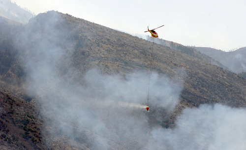 Rick Egan  | The Salt Lake Tribune   A helicopter carries water to the fire in Skull Valley, Saturday, August 17, 2013.