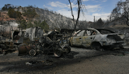 Rick Egan  | The Salt Lake Tribune   A home, cars and ATV's destroyed by the fire in Terra, Utah, Saturday, August 17, 2013.