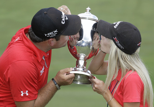 Bob Leverone | The Associated Press Patrick Reed and his wife and caddy, Justine kiss the Sam Snead trophy after he won the Wyndham Championship golf tournament in a second hole playoff at the Sedgefield Country Club in Greensboro, N.C., Sunday, Aug. 18, 2013. (AP Photo/Bob Leverone)