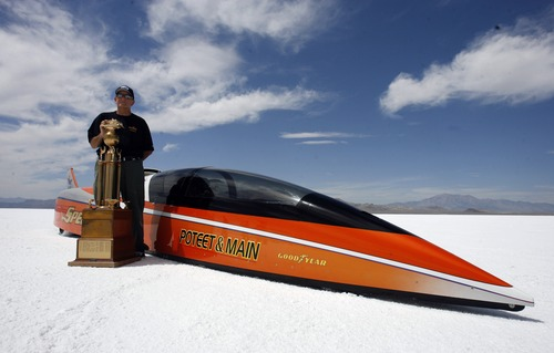 "Rick Egan   |  Tribune file photo George Poteet stands by his car ""Speed Demon"" along with the Hot Rod Magazine Trophy, at the Bonneville Salt Flats during the 2011 Speed Week. This year's Speed Week runs through Friday."