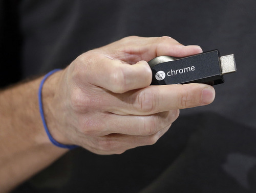 Google's new Chromecast device is shown by Mario Queiroz, vice president for product management, on Wednesday, July 24, 2013, in San Francisco. (AP Photo/Marcio Jose Sanchez)