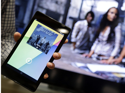 The new Nexus 7 tablet, left, works in conjuction with the Chromecast device to control a television during a Google event on Wednesday, July 24, 2013, in San Francisco. (AP Photo/Marcio Jose Sanchez)