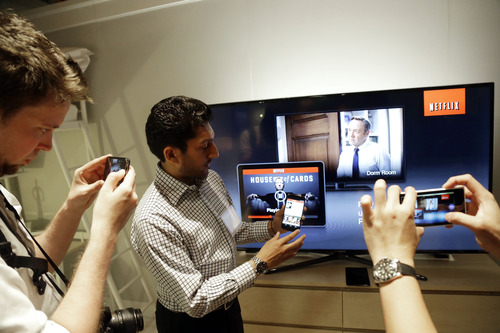 Suveer Kothari, center, displays how the new Chromecast device operates a television with the use of a smartphone during a Google event on Wednesday, July 24, 2013, in San Francisco. (AP Photo/Marcio Jose Sanchez)