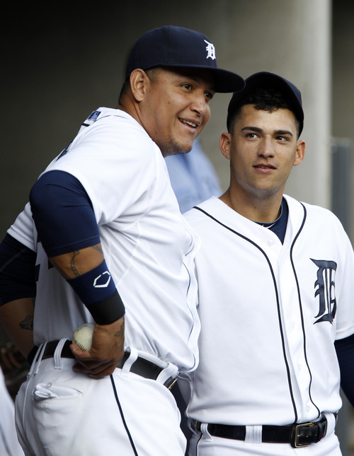 Detroit Tigers' Miguel Cabrera, left, and Jose Iglesias talk in the dugout before a baseball game against the Kansas City Royals, Saturday, Aug. 17, 2013, in Detroit. (AP Photo/Duane Burleson)