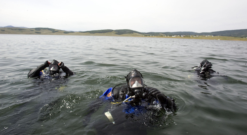 Keith Johnson | The Salt Lake Tribune  Department of Public Safety dive team members Ryan Barney, front, UHP Sgt. Tom Schneiter, left, and UHP Sgt. Wendell Nope prepare to participate in a training exercise at Strawberry Reservoir in Wasatch County, August 7, 2013. Members of the DPS dive team were training with two types of sonar they use in the search and recovery of drowning victims.