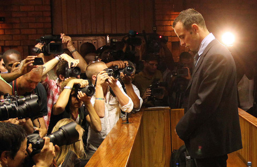 FILE- In this photo taken Friday, Feb. 22, 2013 photographers take photos of Olympic athlete Oscar Pistorius as he stands in the dock during his bail hearing at the magistrates court in Pretoria, South Africa.  According to reports Sunday Aug. 18, 2013, Pistorius is expected to be indicted on a main charge of premeditated murder of his girlfriend, Reeva Steenkamp. on upcoming Monday at Pretoria Magistrate's Court, prosecutors say, confirming they will maintain the charge they initially laid against Pistorius. (AP Photo/Themba Hadebe-FILE)