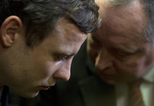 Double-amputee Olympian Oscar Pistorius, left, talks with his lawyer, Kenny Oldwage, right, at the magistrates court in Pretoria, South Africa, Monday, Aug. 19, 2013. Pistorius was indicted Monday on charges of murder and illegal possession of ammunition for the shooting death of the double-amputee Olympian's girlfriend on Valentine's Day.(AP Photo/Themba Hadebe)