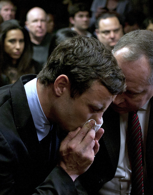 South Africa's Olympian Oscar Pistorius, left, and his lawyer, Kenny Oldwage, right, attend a trial in the magistrates court in Pretoria, South Africa, Monday, Aug. 19, 2013. Pistorius was indicted Monday on charges of murder and illegal possession of ammunition for the shooting death of the double-amputee Olympian's girlfriend on Valentine's Day. (AP Photo/Themba Hadebe)