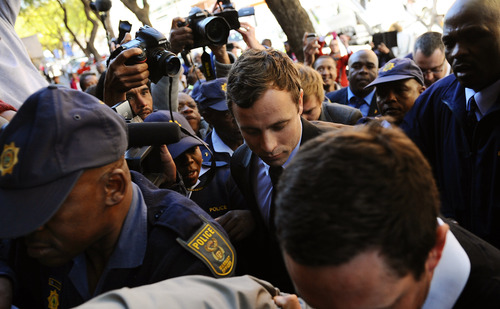 Oscar Pistorius, centre, arrives outside the magistrates court in Pretoria, South Africa, Monday, Aug. 19, 2013.  Pistorius was indicted Monday on charges of murder and illegal possession of ammunition for the shooting death of his girlfriend Reeva Steenkamp. (AP Photo)