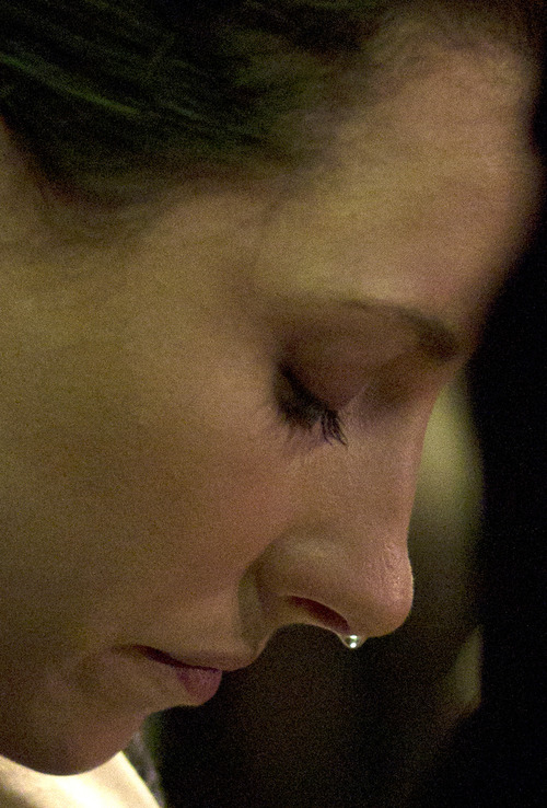 Murder suspect Oscar Pistorius's sister Aimee sheds a tear as she prays with her brother during his appearance at a court in Pretoria, South Africa, Monday, Aug. 19, 2013. Pistorius has arrived at a South African court ahead of the expected indictment of the double-amputee Olympian on a premeditated murder charge. (AP Photo/Themba Hadebe)