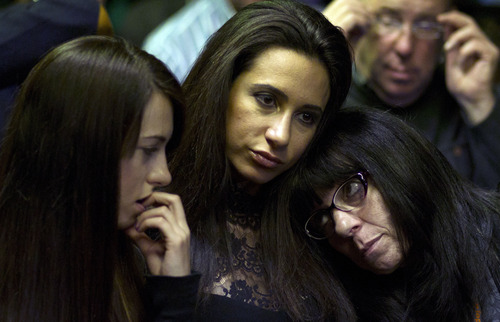 Unidentified friends of Reeva Steenkamp's family look on as double-amputee Olympian, Oscar Pistorius appears in the magistrates court in Pretoria, South Africa, Monday, Aug. 19, 2013.  Pistorius was indicted Monday on charges of murder and illegal possession of ammunition for the shooting death of the double-amputee Olympian's girlfriend on Valentine's Day. (AP Photo/Themba Hadebe)