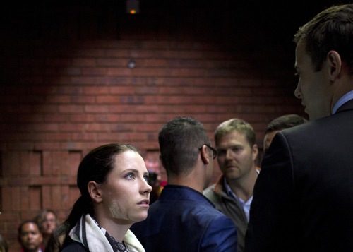 Oscar Pistorius, right, talks with his sister Aimee, left, during his appearance at a court in Pretoria, South Africa, Monday, Aug. 19, 2013. Pistorius arrived at the South African court ahead of the expected indictment of the double-amputee Olympian on a premeditated murder charge. (AP Photo/Themba Hadebe)