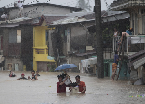 Residents evacuate to higher ground after floodwaters caused by the swelling of a river surround their homes in Marikina city, east of  Manila, Philippines on Tuesday, Aug. 20, 2013. Some of the Philippines' heaviest rains on record fell for a second day Tuesday, turning the capital's roads into rivers and trapping tens of thousands of people in homes and shelters. The government suspended all work except rescues and disaster response. (AP Photo/Aaron Favila)
