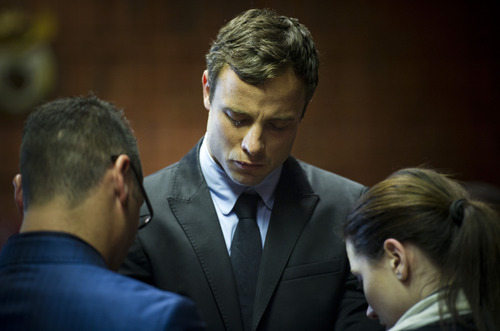 Oscar Pistorius cries as he prays with his sister Aimee and brother Carl in the magistrates court in Pretoria, South Africa, Monday, Aug. 19, 2013.  Pistorius was indicted Monday on charges of murder and illegal possession of ammunition for the shooting death of his girlfriend Reeva Steenkamp. (AP Photo)