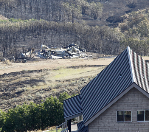 Al Hartmann  |  The Salt Lake Tribune Rockport Estates home is burned down to its foundation while a house across the road survived the Rockport 5 Fire. Residents were allowed to return to their homes Monday August 19.