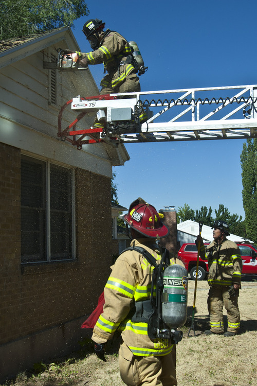 Chris Detrick  |  The Salt Lake Tribune Salt Lake City Capt. Dan Gish and firefighter Kurt Urses watch as firefighter John McNeill cuts a ventilation hole in the gable during a training drill on an old home, which is scheduled to be demolished, in Salt Lake City Wednesday August 21, 2013.