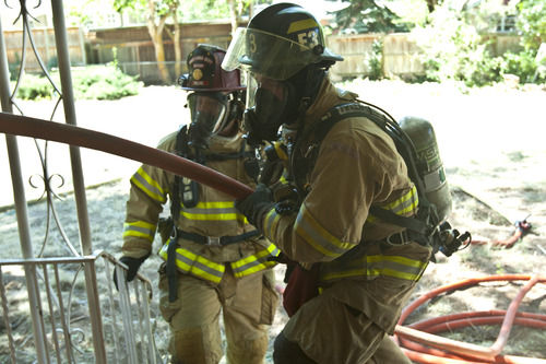 Chris Detrick  |  The Salt Lake Tribune Salt Lake City firefighters Matt Hovermale, right, and Capt. Chris Milne carry in water hoses during a training drill on an old home, which is scheduled to be demolished, in Salt Lake City Wednesday August 21, 2013.