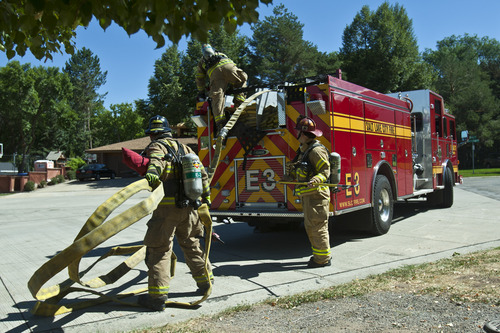 Chris Detrick  |  The Salt Lake Tribune Salt Lake City firefighters, Matt Hovermale, Jonathan Davies and Capt. Chris Milne take out water hoses during a training drill on an old home, which is scheduled to be demolished, in Salt Lake City Wednesday August 21, 2013.