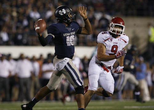 Scott Sommerdorf  |  The Salt Lake Tribune              USU QB Chuckie Keeton throws while being watched by Utah LB Trevor Reilly during second half play. The USU Aggies beat Utah 27-20 in OT, Friday, September 7, 2012.