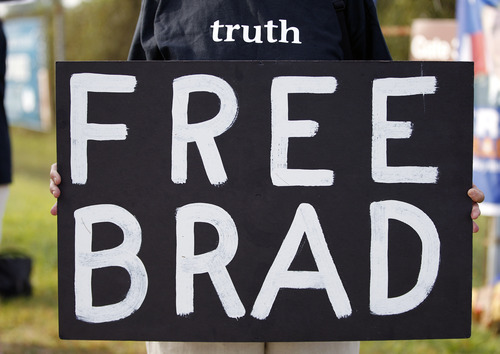 A supporter of Army Pfc. Bradley Manning holds a sign as they protest outside of the gates at Fort Meade, Md., Wednesday, Aug. 21, 2013, before a sentencing hearing of Manning's court martial. The military judge overseeing Manning's trial said she will announce on Wednesday his sentence for giving reams of classified information to WikiLeaks.  (AP Photo/Jose Luis Magana)