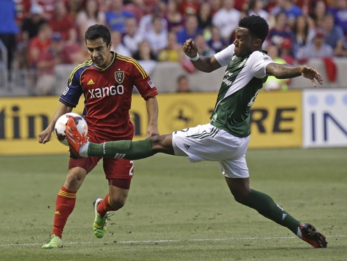 Real Salt Lake's Tony Beltran (2) watches as Portland Timbers' Rodney Wallace, right, kicks the ball in the first half of a U.S. Open Cup soccer game Wednesday, Aug. 7, 2013, in Sandy, Utah. (AP Photo/Rick Bowmer)