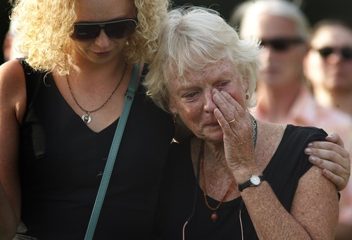 Leah Hogsten | The Salt Lake Tribune Brooke Hopkins' caregiver and student nurse Jackie Calhoon whispers her condolences to Peggy Battin at the graveside of her husband, Aug. 2, 2013.