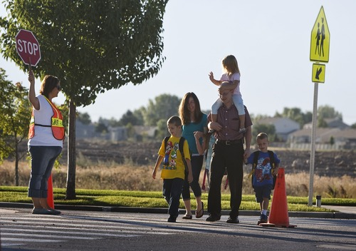 Leah Hogsten | The Salt Lake Tribune Neil Armstrong Academy students, fifth-grader Dayah Ostler and her siblings, third-grader Porter and first-grader Ethan, walk to school with their mother Alison, father Doug and sister Kaitlyn, age 3 on the first day of school, Wednesday, August 21, 2013.