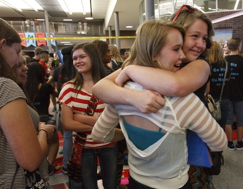 Leah Hogsten | The Salt Lake Tribune Ninth-grader Madison Tagge (right) bear hugs her friend Mikala Gehlen on their first day at Granger High School. Granger High School welcomed returning students and 1,500 new students with a red carpet welcome, lined by cheering school ambassadors and teachers, Wednesday, August 21, 2013.