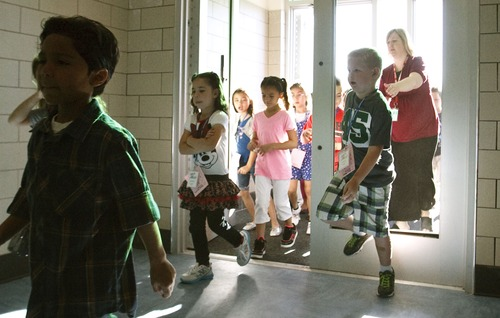 Leah Hogsten | The Salt Lake Tribune Neil Armstrong Academy students walk through the school door without glass on the first day of school, Wednesday, August 21, 2013. The school is still under construction.